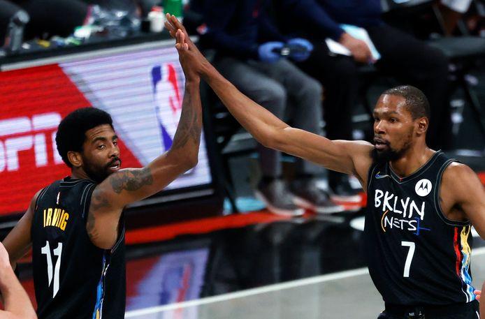 Kevin Durant (r) krijgt een high-five van ploeggenoot Kyrie Irving.