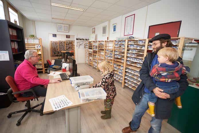 Jeroen Snijders Blok (links) helpt een lid van de Legotheek.  Hij bevindt zich op veilige afstand van Menso Kuik, zijn zoon Ilias en dochter Nuri.