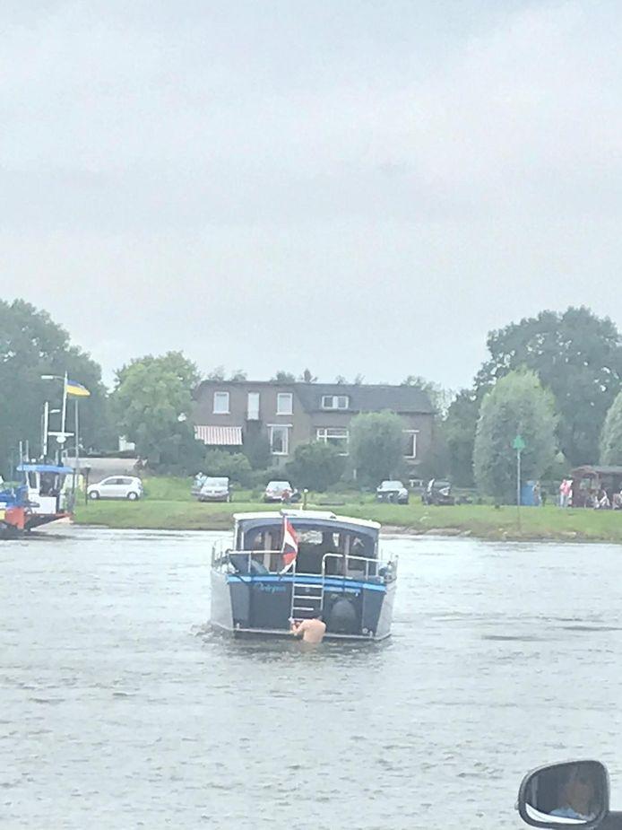 De schipper van het vastgelopen bootje probeert deze van onder los te maken. Een gevaarlijke operatie met de sterke stroming die in de IJssel staat.