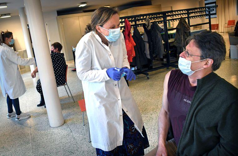 Huisarts Trudie Oldenhuis maakt een grapje tijdens het vaccineren met AstraZeneca in een kerk in Groningen.  Beeld Marcel van den Bergh / de Volkskrant