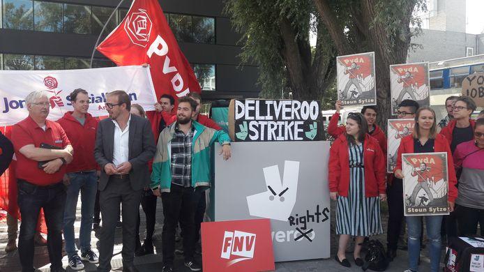Leden van FNV Jong en de PvdA waren met bezorgers van Deliveroo en Foodora naar Amsterdam gekomen om bezorger Sytze Ferwerda (groene jas) te steunen. Links naast hem PvdA-Kamerlid Gijs van Dijk.