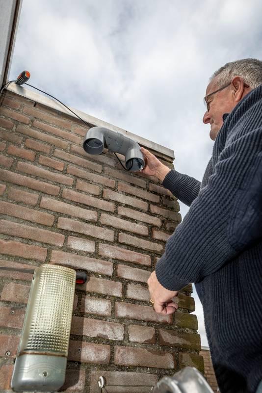 Martin van den Heuvel van het Repaircafé Rijpelberg monteert de eerste zelfgemaakte fijnstofmeter aan de woning van Johan Megens.