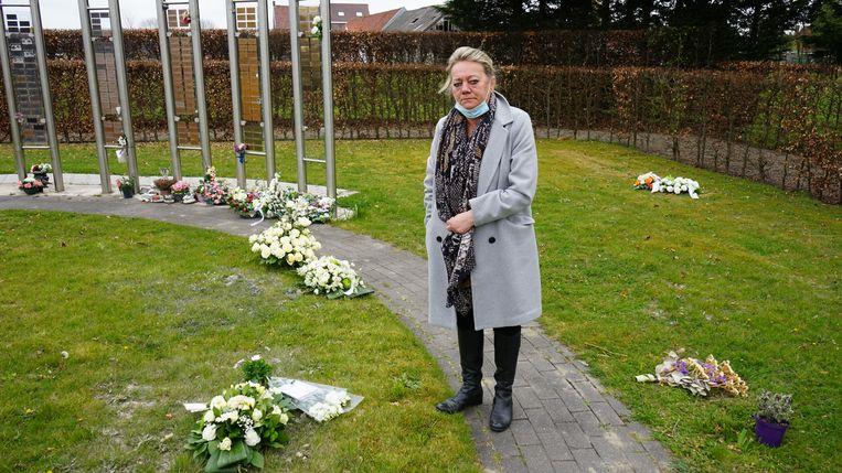 Marina bij de laatste rustplaats van haar moeder. Het enige bloemstuk dat ze terugvonden onder de wielen van een vrachtwagen, hebben ze teruggelegd. Beeld Kristof Pieters