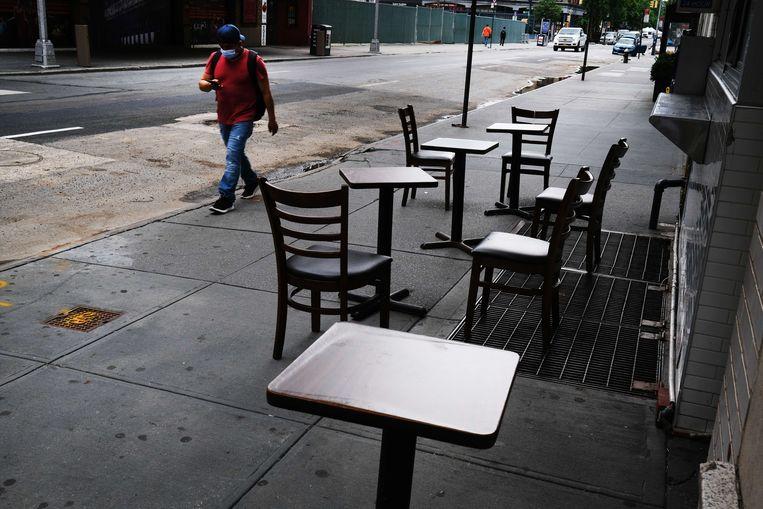 Een man loopt langs een leeg terras in New York. Beeld AFP