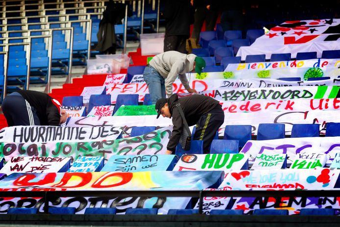 Feyenoord-supporters bedekken de stoeltjes in de Kuip met spandoeken. Op deze manier willen de fans de spelers ondersteunen tijdens de thuiswedstrijden.