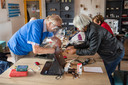 Willem Rapati van het Repair Café en Cécile Boogerd sleutelen aan de Singer naaimachine van Cécile