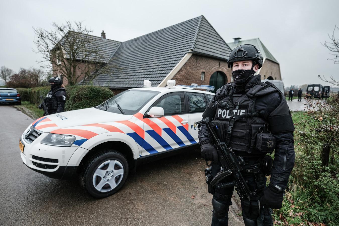 Zwaarbewapende agenten bewaken de locatie van het drugslab in Baak tijdens de ontmanteling daarvan begin december vorig jaar.