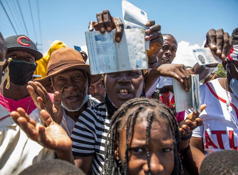 Haitianen tonen hun persoonsbewijzen bij de Amerikaanse ambassade, in de hoop asiel te krijgen. Beeld AFP