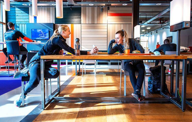 Zevenkamper Anouk Vetter (links) en hordenloper Nadine Visser (rechts) hebben schik tijdens lunchtijd in het topsportrestaurant van Papendal. Beide vrouwen bereiden zich voor op de Zomerspelen, waar ze kans maken op een atletiekmedaille. Het is nog 270 dagen tot Tokio. Beeld Klaas Jan van der Weij