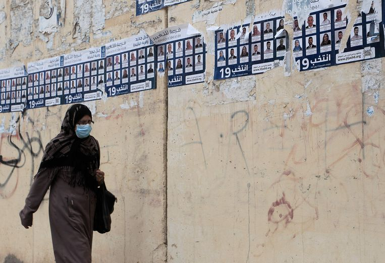 Een vrouw loopt voorbij verkiezingsposters in de hoofdstad Algiers. Beeld AFP