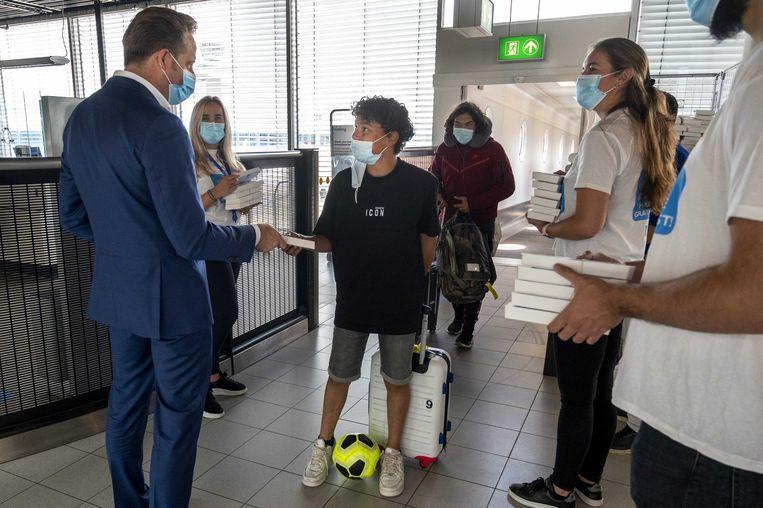 Demissionair minister Hugo de Jonge (Volksgezondheid) deelt samen met de GGD Kennemerland covidzelftesten uit aan jongeren die terugkeren van vakantie.  Beeld ANP