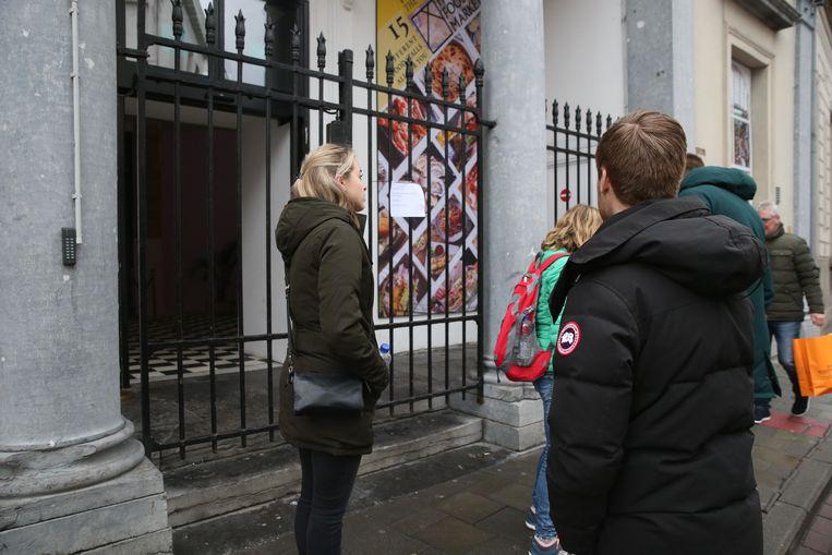 Enkele klanten staan voor de gesloten deur van de Holy Food Market.