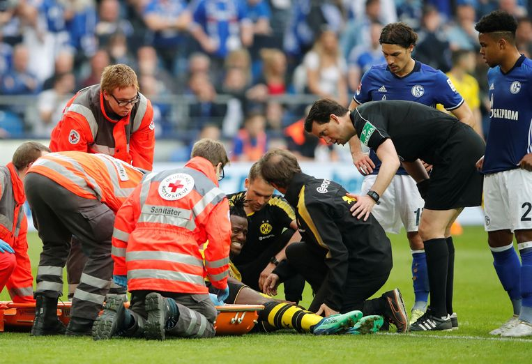 Dortmund-aanvaller Michy Batshuayi krijgt verzorging tijdens de derby tegen Schalke. Hij scheurde enkele ligamenten. Beeld Photo News