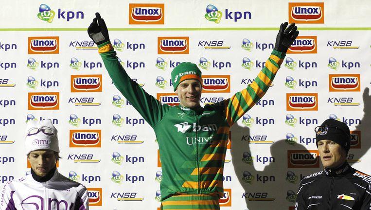 Winnaar Bob de Vries temidden van Christijn Groeneveld (L) en Martijn van Es (R) op het podium. De Vries won de eerste marathon op natuurijs van het seizoen, in Noordlaren. Foto ANP Beeld