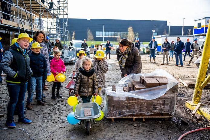 De eerste steen van de nieuwbouw basisschool De Olijfboom is gelegd. Leerlingen helpen mee. De school gaat in januari 2022 open.