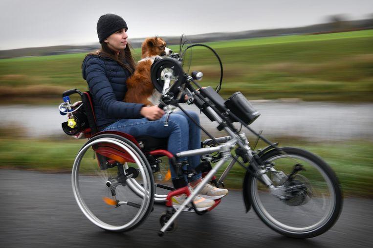 Celine Hermans en haar 'schoothondje' Holly op de handbike. Beeld Marcel van den Bergh / de Volkskrant