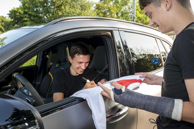 Steven Berghuis geeft zijn handtekening aan een fan bij trainingscomplex De Toekomst na zijn eerste training bij Ajax. De aanvaller is overgestapt van Feyenoord naar de landskampioen.  Beeld ANP