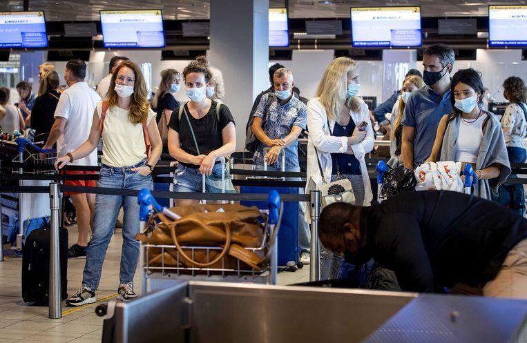 Incheckbalies van KLM op Schiphol. Nu de coronamaatregelen steeds meer worden versoepeld, verwacht de luchthaven deze zomer een fors aantal reizigers. Beeld ANP
