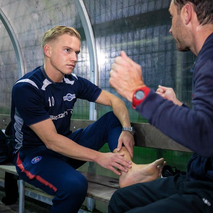 Wouter van Heertum in overleg met fysiotherapeut Michel van Avanti'31. Hij raakte afgelopen zondag geblesseerd aan zijn knie en enkel.