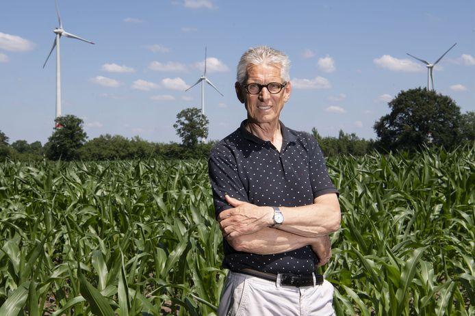 Hans te Grotenhuis, voorzitter Burgerwindcoöperatie Achterhoekse Wind Energie UA, met op de achtergrond windmolens bij Lünten.