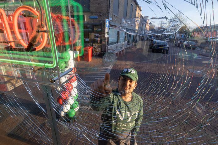 Jamal Hadou wijst verbolgen naar zijn door bakstenen beschadigde winkelpui.