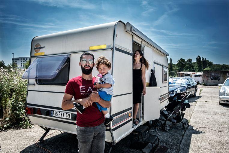 Een jonge vader staat voor zijn caravan op het terrein aan de Dantestraat in Anderlecht.  Beeld Tim Dirven