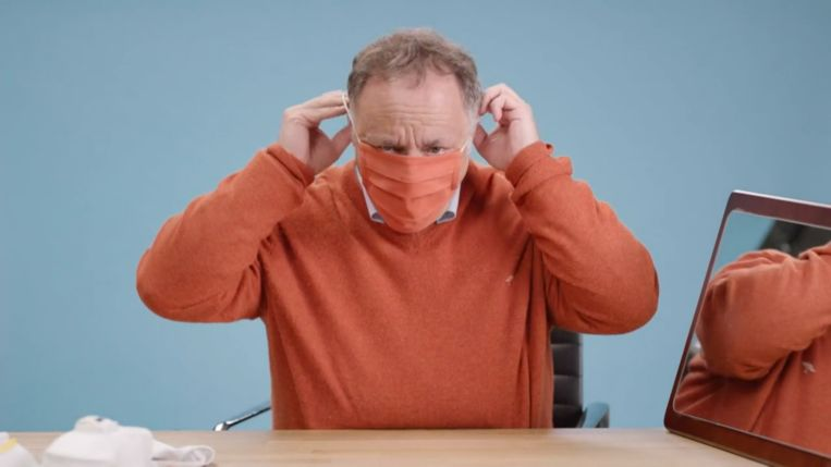 Marc Van Ranst demonstreert hoe je een mondmasker gebruikt. Beeld rv