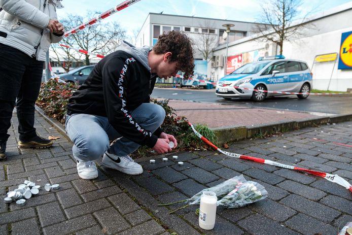 Buurtbewoners leggen kaarsen en bloemen neer op de plaats van de aanslag.
