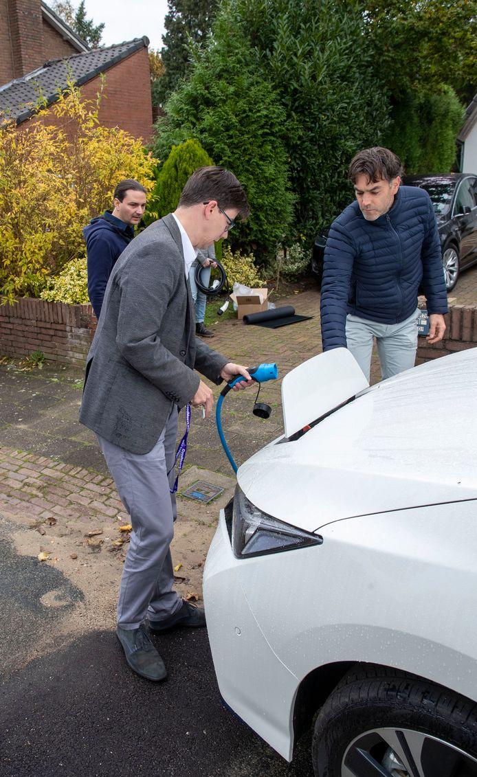 Wanka Lelieveld (rechts) helpt wethouder De Haan bij het opladen van de deelauto.