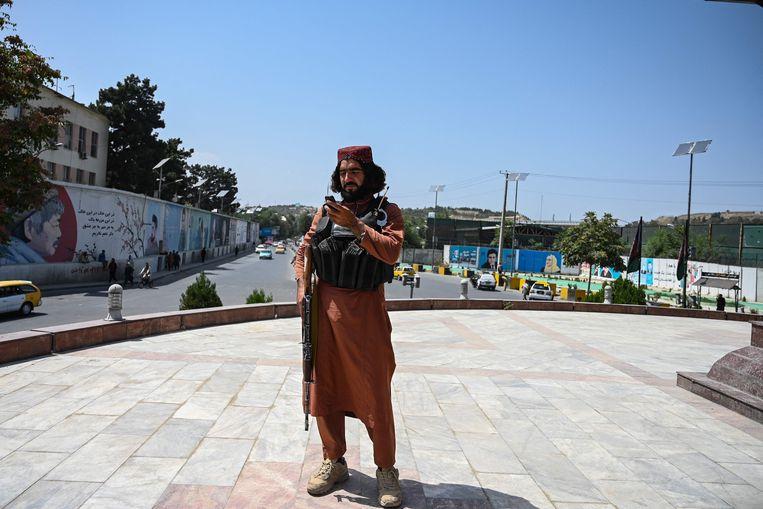 Een Taliban-strijder houdt de wacht op het Massoud-plein in Kaboel op 16 augustus 2021.  Beeld AFP