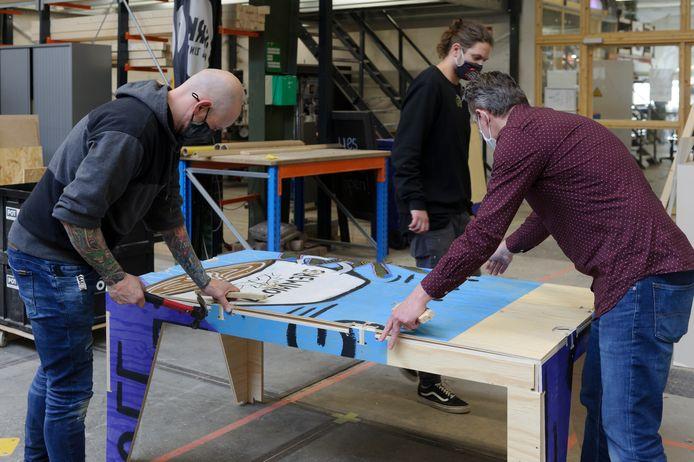Jan-Henk van Ieperen (links) en Stefan van Ham leggen in het gebouw van SPARK Makers Zone de laatste hand aan een tafel. In het midden Frank Willems.