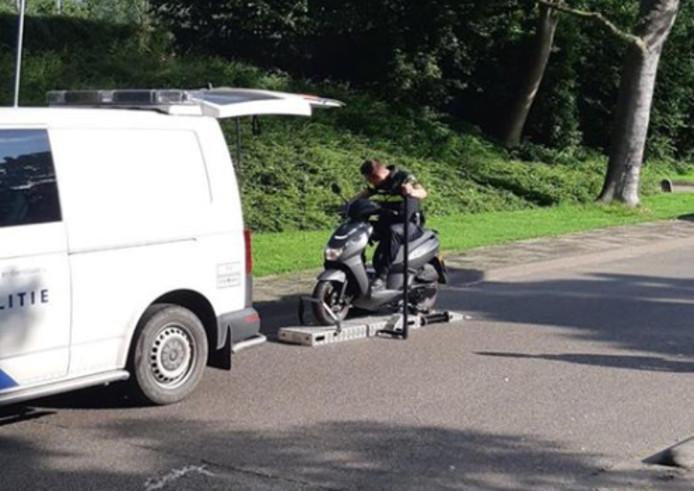 Een agent zet een scooter op de rollerbank.