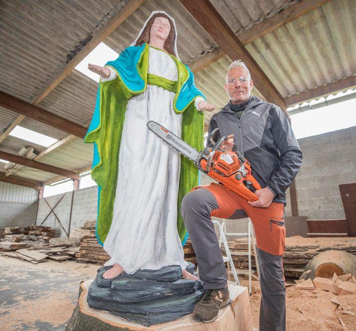 Peter Verlaan bij het Mariabeeld dat hij met een kettingzaag maakte uit een oude beuk.
