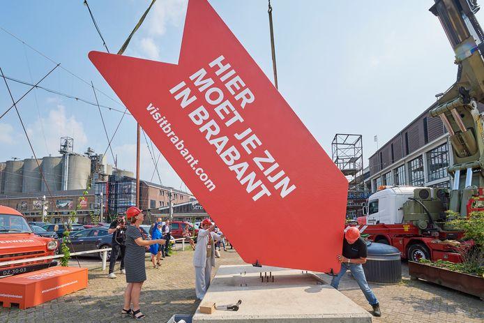 Plaatsing van de grote rode pijl  'Hier moet je zijn in Brabant' op de Noordkade in Veghel door directrice van VisitBrabant Heleen Huisjes (links) en wethouder Coby van der Pas (midden onder de pijl).