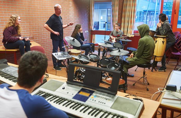 Roger Niese helpt de leerlingen met het componeren van hun muziekstuk.