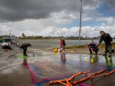 Tekenen voor de vrede op de veerstoep in Wamel, tussen de regen- en hagelbuien door