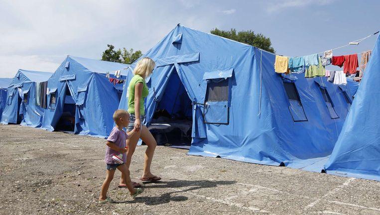 Een moeder en kind lopen door een tijdelijk vluchtelingenkamp in Oost-Oekraïne Beeld AFP