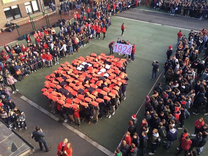 De leerlingen vormden samen een rode neus op de speelplaats. Trots houden ze een bord op met daarop de ingezamelde som geld.
