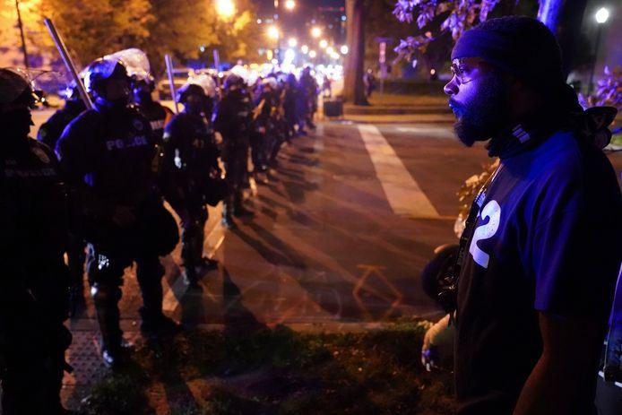 Een demonstrant staat oog in oog met een politiecordon in Louisville, tijdens betogingen tegen de beslissing om maar één agent te vervolgen voor de dood van Breonna Taylor.