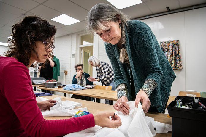 Docenten Martine Bruil (r.) en Karin Janssen (geblokt vest) leren cursisten de fijne kneepjes.