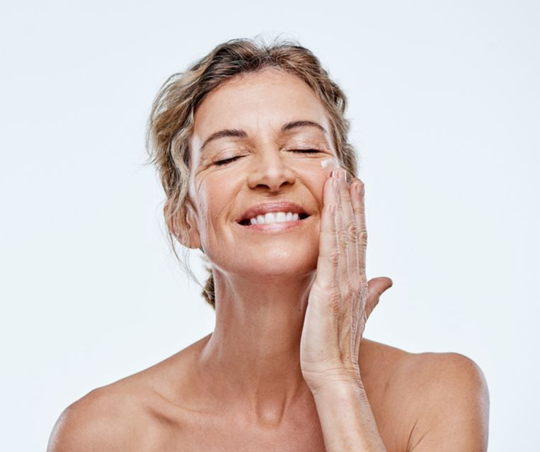 Shot of a mature woman posing with moisturiser on her face Beeld Getty Images