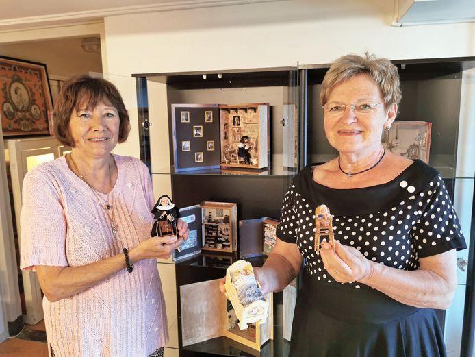 Corrie de Hoon met in haar hand een nonnetje en Corrie van den Broek toont een bedje en een kinderstoel. Hun miniatuurpoppenhuizen zijn te bezichtigen in het schoolmuseum Schooltijd in Terneuzen.