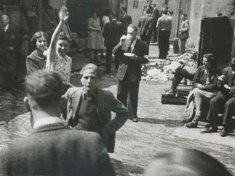 Joodse vrouw zwaait naar haar vriendin op de verzamelplaats voor te deporteren Joden bij de Hollandsche Schouwburg. Beeld Foto: L. van Nobelen-Riezouw / NIOD