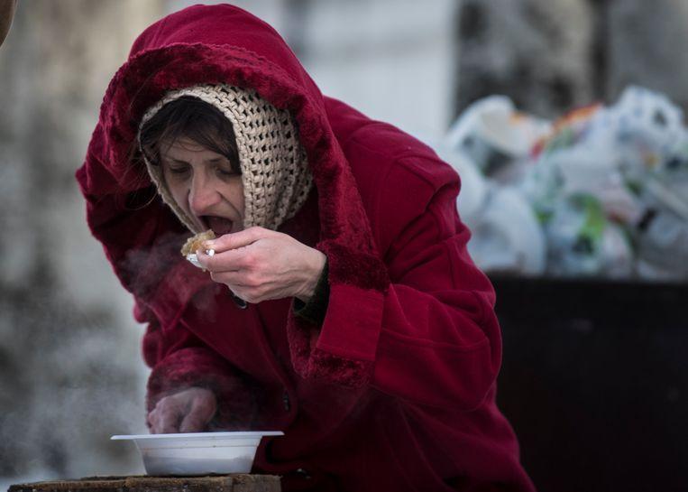 Een vrouw eet een gratis maaltijd in een hulpcentrum in Avdiivka, in het oosten van Oekraïne.  Beeld AP