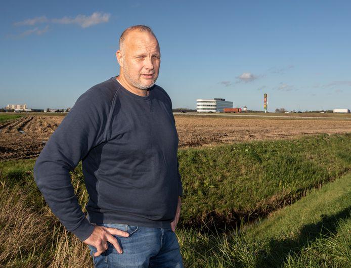 Jan-Kees de Meester met op de achtergrond het kantoorpand van Roompot en de hoge zuil van de fastfoodboulevard bij Goes.