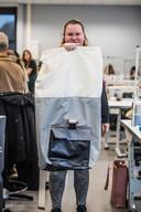 Een student van Rijn IJssel toont de tas waarin de sheltersuit kan worden opgeborgen.