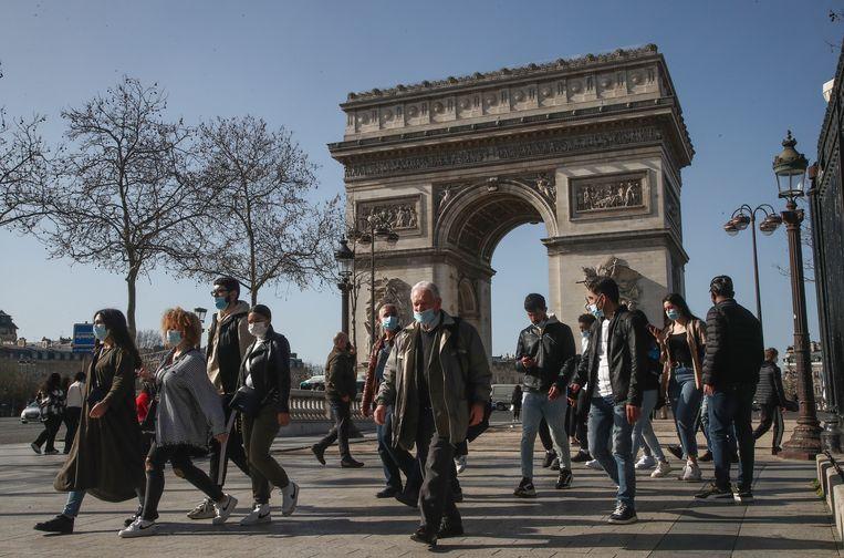 Mensen met mondkapjes bij de Arc de Triomphe in Parijs. Beeld AP