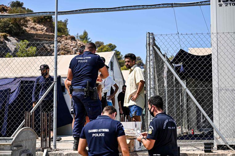 De Griekse politie deelt voedsel uit aan migranten in het quarantainegedeelte van het kamp op het eiland Lesbos. Beeld AFP