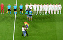 A protestor is apprehended by security after he ran onto the field holding a Rainbow Flag and stood in front of the Hungarian team during Hungary's national anthem before the Euro 2020 soccer championship group F match between Germany and Hungary at the football arena stadium in Munich, Germany, Wednesday, June 23, 2021. (Matthias Hangst/Pool Photo via AP)
