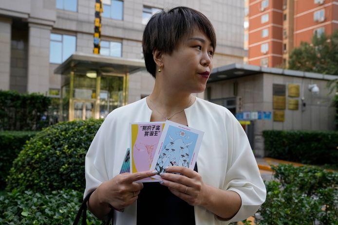 """Teresa Xu toont kaartjes aan de pers met het opschrift """"mijn baarmoeder, mijn keuze"""". De vrouw krijgt vandaag na twee jaar een tweede hoorzitting in de rechtbank van Peking om te strijden voor het recht om als ongetrouwde vrouw haar eicellen te laten invriezen."""